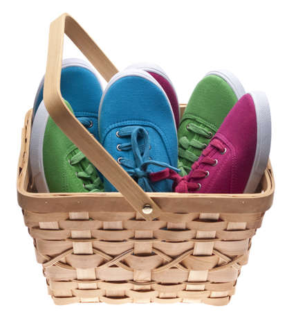needy: A basket of child sized shoes, concept for giving clothing to the needy.  Isolated on White