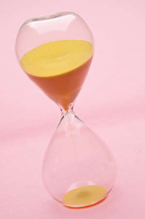 Modern Hour Glass with Yellow Sand on a Pink Background.  Time is Passing as the Sand Falls. Stock Photo