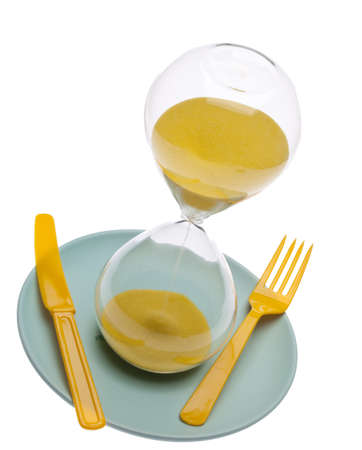 Hourglass on a plate with a fork and knife for food and time conceptual themes. Stock Photo