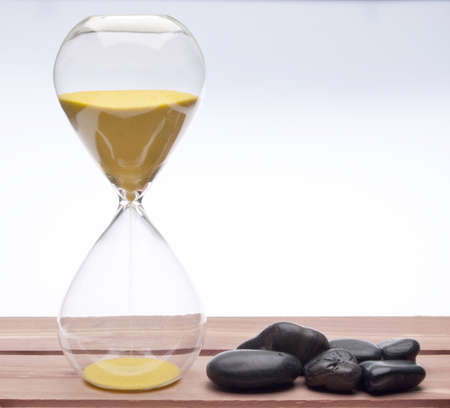 pass away: Hourglass and Massage Stones for a Time to Relax Concept.