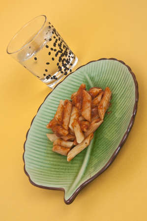 seltzer: Ziti Dinner on a Green Dish with a Glass of Seltzer Water on a Yellow Background. Stock Photo