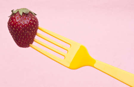 Fresh Summer Strawberry on a Vibrant Yellow Fork. photo