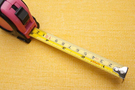 Measuring Tape for Women that is  Pink Colored on a Vibrant Yellow Background. Stock Photo