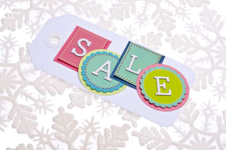 Holiday Sale Tag on a Snowflake Background. Stock Photo