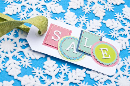 Sale Tag on a Winter Holiday Snowflake Background. Stock Photo