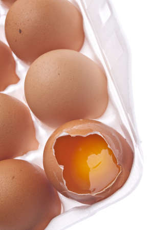 Fresh Organic Brown Eggs in a White Carton with One Cracked Egg. photo