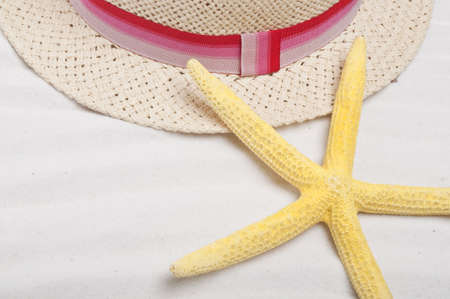 Beach Background with Hat and Bright Yellow Starfish.