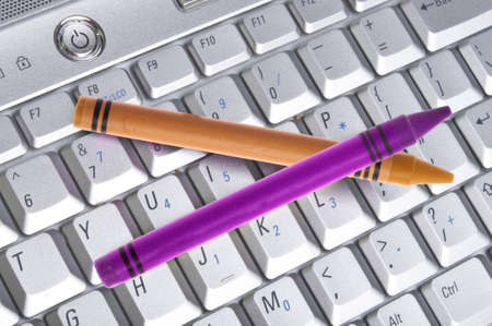 originative: Pair of Crayons on a Computer Keyboard for Creative Computing Concepts.
