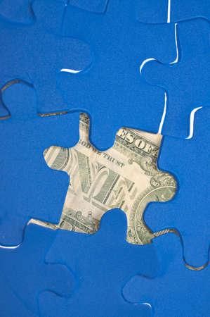originative: Financial Puzzle Money Under a Puzzle Game. Stock Photo