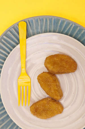 Chicken Nuggets on a Modern Place Setting with a Yellow Fork.