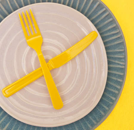 concave: Modern Place Setting with Empty Plate and Plastic Yellow Silverware on Yellow Background.