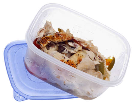 Leftover Roasted Chicken with Vegetables in a Plastic Storage Container with Lid Isolated on White. photo