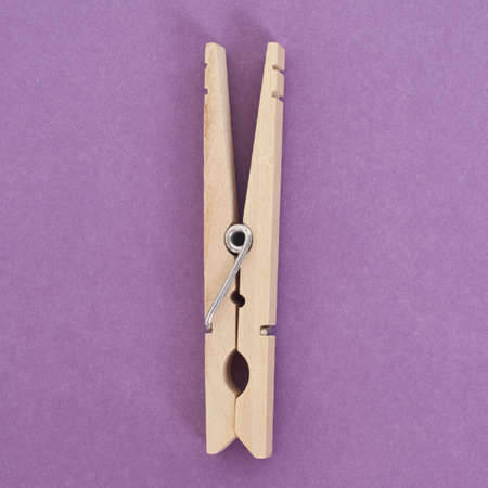 mundane: Simple Clothespin in a Modern Setting on Vibrant Purple. Stock Photo