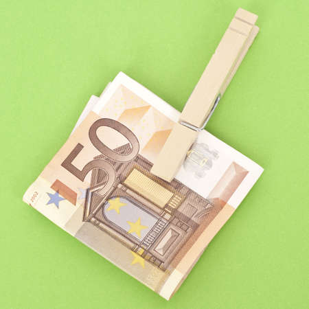mundane: Euro Currency in a Clothespin on Vibrant Green.  Money Concept. Stock Photo