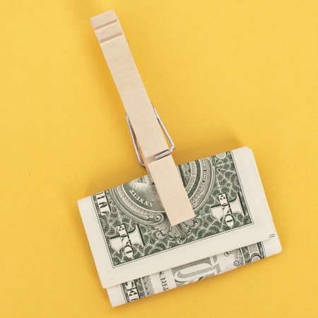 American Currency in a Clothespin on Vibrant Yellow.  Money Concept. Stock Photo - 8135181
