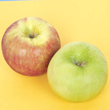 Fresh Healthy Pair of Apples in Red and Green on Vibrant Yellow. Stock Photo
