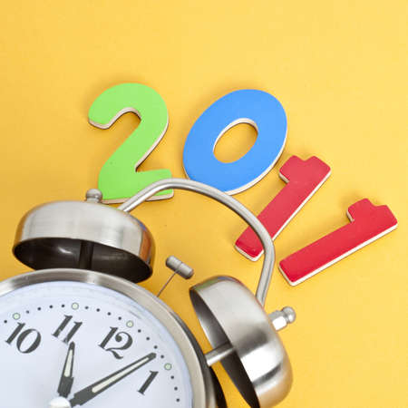 Time for 2011 Concept with Clock and 2011 Focus on 2011 on Vibrant Yellow. Stock Photo - 8135221
