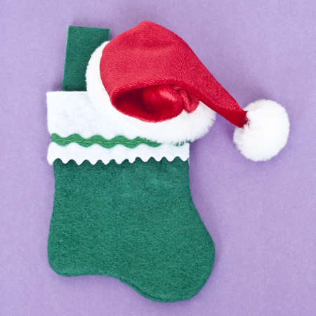 mundane: Holiday Stocking with a Red Holiday Hat on Vibrant Purple. Stock Photo