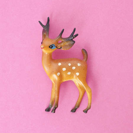 mundane: Vintage Deer Holiday Toy on a Vibrant Pink Background. Stock Photo