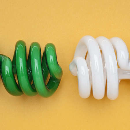 Compact Fluorescent Engery Saving Light Bulbs in Green and White on an Orange Background. photo