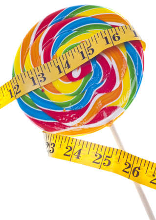 Diet Challenge Concept with Candy Lollipop and Measuring Tape.  Isolated on White with a Clipping Path. photo