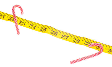 Holiday Diet Concept with Candy Cane Candies and Measuring Tape Isolated on White  Zdjęcie Seryjne