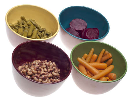 Variety of Canned Vegetables in Bowls including Carrots, Beets, Asparagus and Black Eyed Peas.  Isolated on White. photo