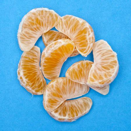 clementine fruit: Clementine Slices on Vibrant Blue Fresh Juicy Fruit Image.