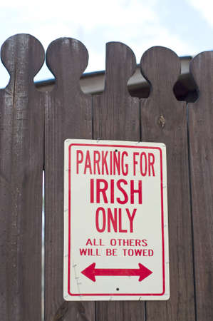 towed: Parking for Irish Only Sign on an Old Fence. Stock Photo