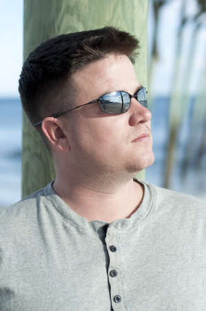 Brown Haired Man with Sunglasses Looking Away at the Beach. photo