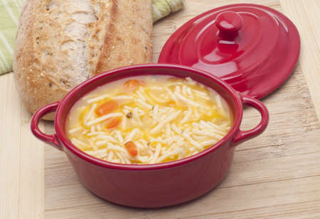 chicken noodle soup: Classic Chicken Noodle Soup in a Crock with Bread in the Background.