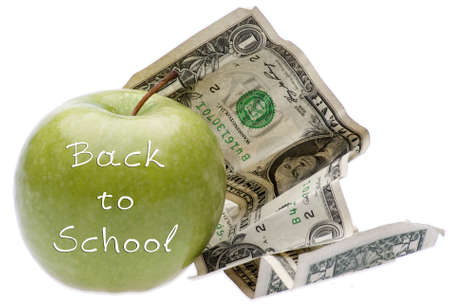 current events: An apple with money symbolizes the cost involved education. Stock Photo