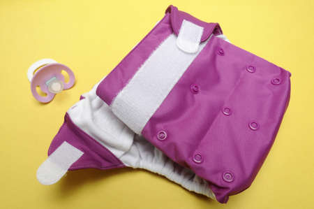 Open Eco Friendly Cloth Diaper with Dummy on Yellow Background photo