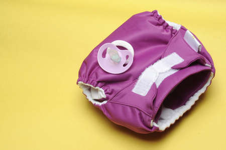 Eco Friendly Cloth Diaper with Dummy on Yellow Background photo