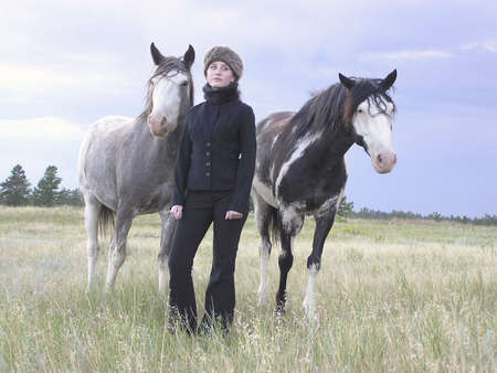 intrigue: girl in black with fur hat standing in a field with horses Stock Photo