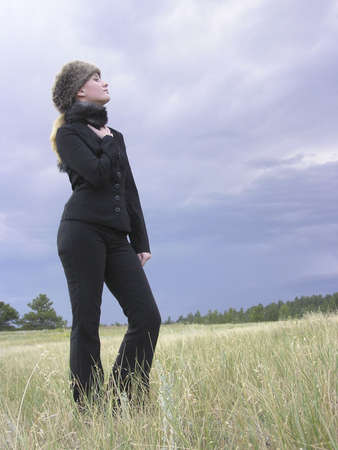 intrigue: girl in black with fur hat standing in a field