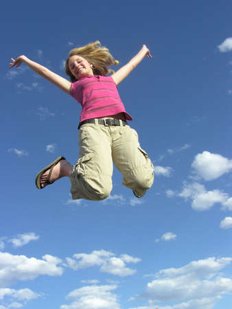 gaiety: Teen jumping for joy in cloud background Stock Photo