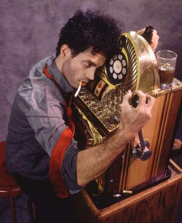 bedraggled: Gambler at slot machine Stock Photo