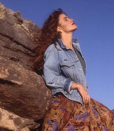 Dreamy girl leaning on rocks photo