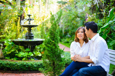 Young asian couple holding hands in the garden with fountain photo