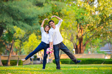 destination wedding: Young asian couple making heart with their arms Stock Photo