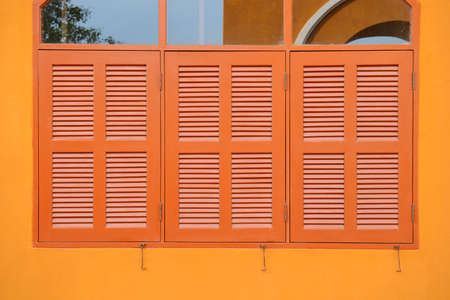 building feature: Wooden window shutter of an orange house