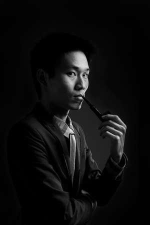 photography background: Portrait of a young man smoking a pipe Stock Photo