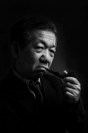 senior smoking: Portrait of a senior man smoking a pipe Stock Photo