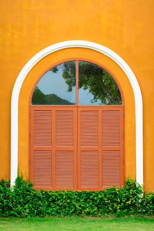 showcase interiors: Window shutter of an orange house with grass Stock Photo