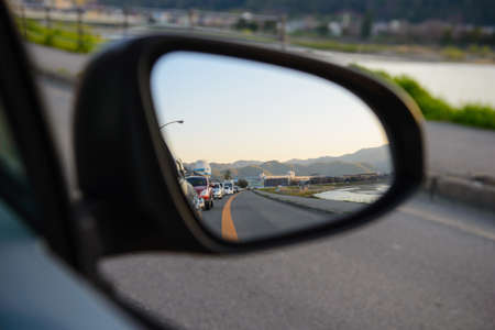 Rear view mirror reflecting a line of cars behind Imagens