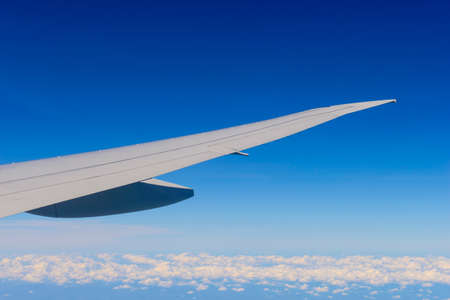 Passenger view from airplane flying over clouds Stock Photo