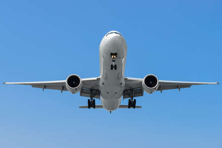 finals: Commercial airplane on finals runway against blue sky