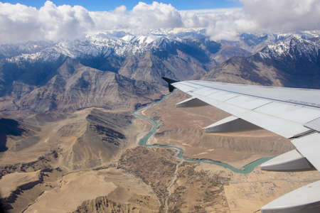 leh: Airplane wing with Leh city and Himalayas mountain