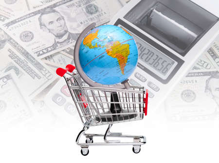 Earth on shopping cart with calculator and dollars background